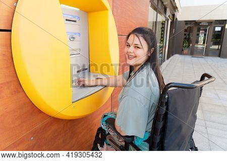 Happy Disabled Handicapped Woman In Wheelchair Using Atm Cash Macjine And Smiling At Camera On Sunny