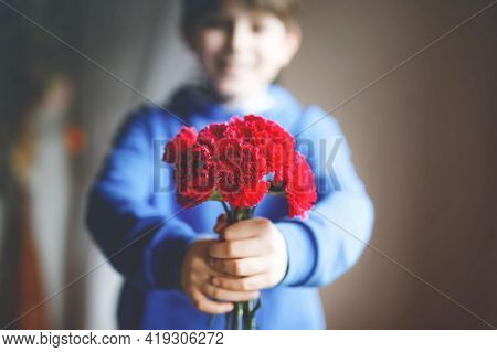 Closeup Of Hands Of Preteen Kid Boy Holding Bunch Of Clove Flowers. Child Congrats And Presents Clov