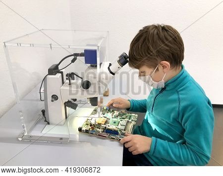 Kid Boy Conducts Experiment With Microscope In School Lab. Curious Inquisitive Child Learning Physic