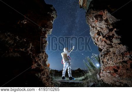 Back View Of Spaceman In White Suit And Helmet Standing And Exploring Beautiful Starry Sky At Night.