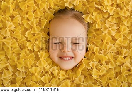 A Large Pile Of Dry Noodles In The Form Of A Bow. Pasta Made From Durum Wheat. The Child's Face Is S