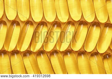 Fish Oil Softgels In A Row, Omega 3 Capsules, Yellow Geometric Background.