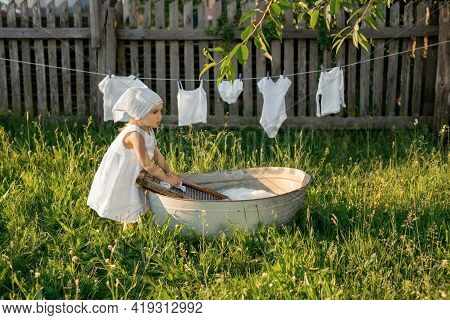 The Child Merrily Washes His Clothes In The Basin. Splashes Of Water And Foam From Washing Clothes.