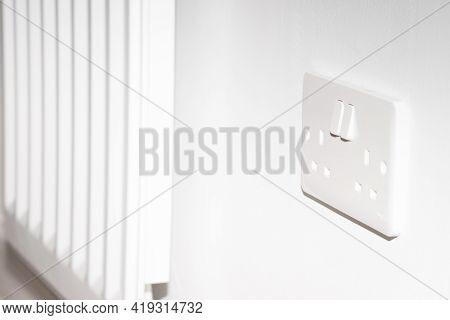 A United Kingdom Standard Wall Socket On A White Wall Next To Radiator