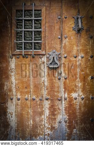 Ancient Wooden Door With A Metall Lattice. Close Up