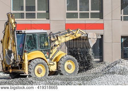 A Yellow Excavator Pours Gray Rubble For Road Repair In The City In Sunny Day