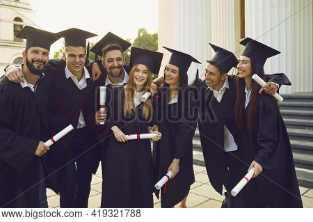 Group Of Positive Students University Graduates Mates Standing, Hugging And Holding Diplomas In Hand