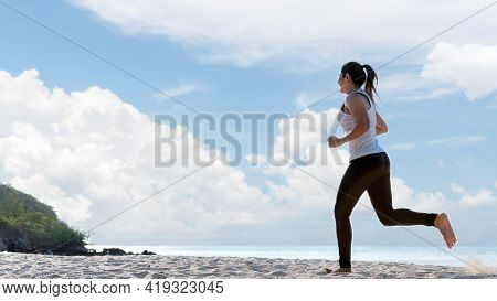 Athletic Woman Jogging Exercise And Relax And Freedom On Sand Beach. People Running And Workout Blue