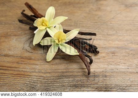 Aromatic Vanilla Sticks And Flowers On Wooden Table, Closeup