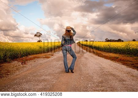 Aussie Country Girl Wearing Demin Jeans And Jacket Standing In Middle Of A Dirt Road In Farm Fields