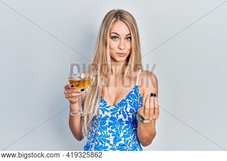 Young beautiful caucasian woman drinking a glass of white wine doing money gesture with hands, asking for salary payment, millionaire business