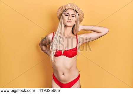Young caucasian woman wearing bikini and summer hat suffering of neck ache injury, touching neck with hand, muscular pain