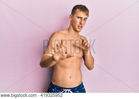 Young caucasian man wearing swimwear disgusted expression, displeased and fearful doing disgust face because aversion reaction. with hands raised