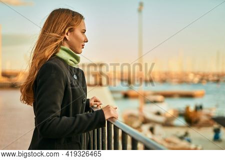 Young blonde girl smiling happy leaning on the balustrade at the city.