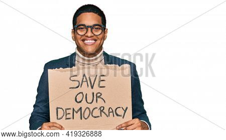 Young handsome hispanic man holding save our democracy protest banner looking positive and happy standing and smiling with a confident smile showing teeth