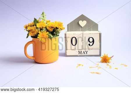 Calendar For May 9: Cubes With The Numbers 0 And 9, The Name Of The Month Of May In English, A Bouqu