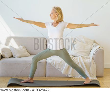 Calm And Concentrated Senior Woman In Home Wear Practicing Warrior Yoga Pose While Exercising In Mor