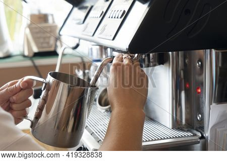 Working Process In Coffee Shop. Cropped Shot Of Barista Heating And Whipping Milk In Metallic Pitche