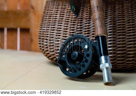Close Up Of Fly Fishing Rod With Reel Next To Braided Basket. Fly Fishing Equipment Still Life. Nobo