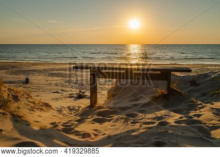 Empty Wooden Bench And Beautiful Golden Sunset At The Beach. Sun Setting Into The Sea On Tranquil Ev