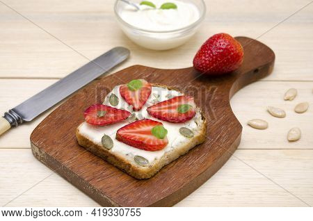 Appetizing Toast With Cream Cheese And Strawberries And Pumpkin Seeds On A Board