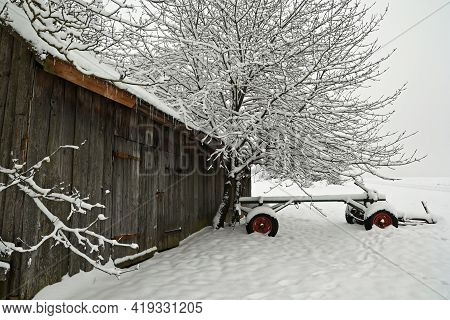 Agricultural Machinery In A Peasants Yard Covered With Fresh Snow