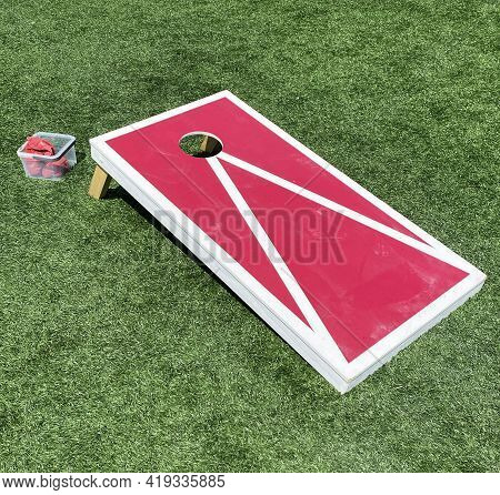 Red And White Bean Bag Toss Cornhole Game On A Green Turf Field.
