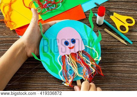The Child Is Holding Puppet Stics Toy Octopus On A Wooden Table. Handmade. Childrens Creativity Proj