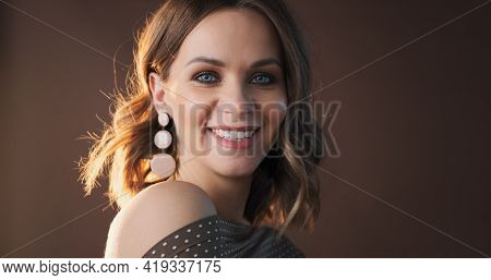 Portrait of young caucasian woman on brown background