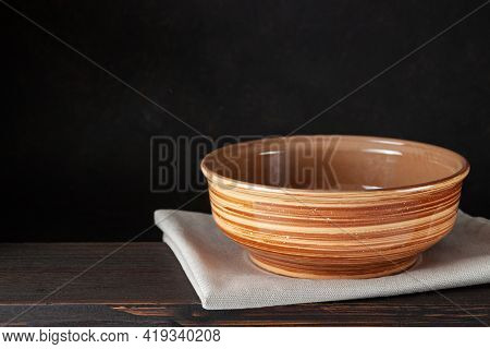 Empty Bowl Plate On Wooden Table Over Dark Brown Background -can Be Used For Display Or Montage Your