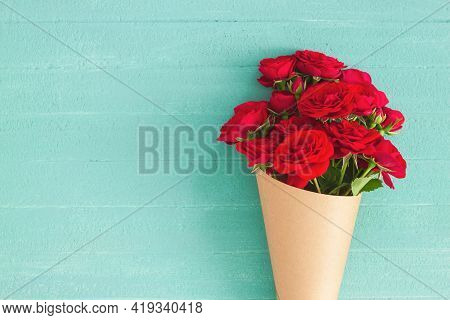 Red Rose Bouquet Wrapped Vintage Craft Paper. Greeting Card For Holiday Text. Top View, Flat Lay