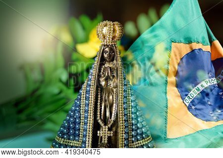 Statue Of The Image Of Our Lady Of Aparecida, Mother Of God In The Catholic Religion, With Brazil Fl