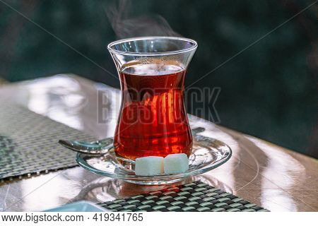 Closeup Of Traditional Turkish Glass Cup, Bardak, Of Turkish Black Tea With Sugar And Spoon