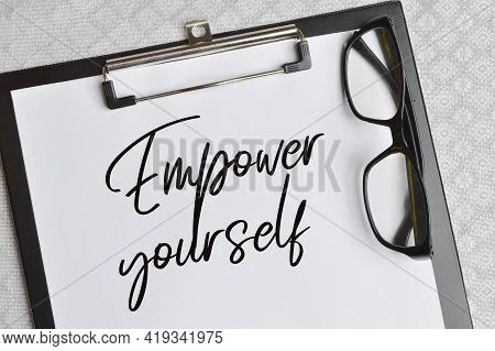 Top View Of Eyeglasses And White Paper Written With Text Empower Yourself