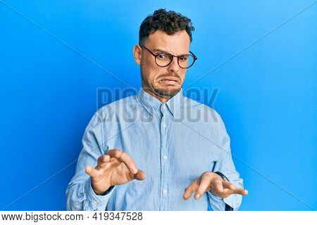 Young hispanic man wearing casual clothes and glasses disgusted expression, displeased and fearful doing disgust face because aversion reaction.