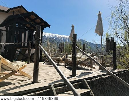 A Terrace In A Wooden Chalet In The Mountains Of Uzbekistan With A Beautiful View Over The Flowering