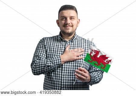 White Guy Holding A Flag Of Wales And Holds His Hand On His Heart Isolated On A White Background Wit