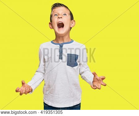 Adorable caucasian kid wearing casual clothes crazy and mad shouting and yelling with aggressive expression and arms raised. frustration concept.