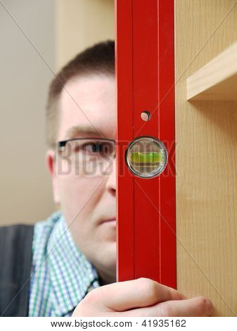 Closeup shot of carpenter looking at spirit level gauge to check verical positioning of furniture - shallow depth of field