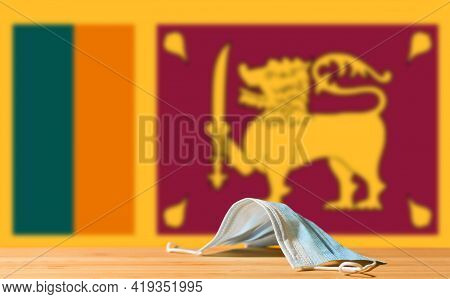 A Medical Mask Lies On The Table Against The Background Of The Flag Of Sri Lanka. The Concept Of A M