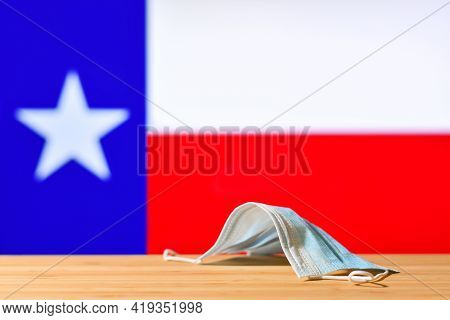 A Medical Mask Lies On The Table Against The Background Of The Flag Of Texas. The Concept Of A Manda