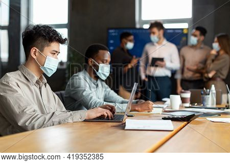 Colleagues Having Meeting In Boardroom, Working On A Project