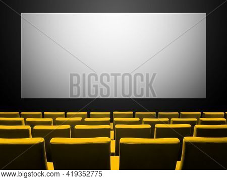 Cinema Movie Theatre With Yellow Velvet Seats And A Blank White Screen. Copy Space Background