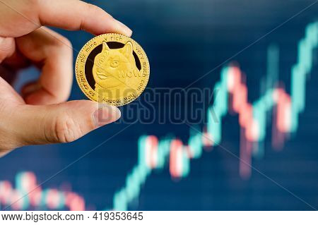 Hand Holding Gold Dogecoin With Blurred Candlestick Chart In The Background. Doge Is The Most Popula