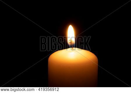 Fire Wax Candle On A Black Background. The Flame Of A Burning Candle In The Dark. One Burning Candle