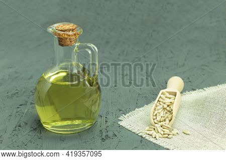 Raw Sunflower Seeds And Sunflower Oil. Seeds And Sunflower Oil On A Wooden Background. Place For You