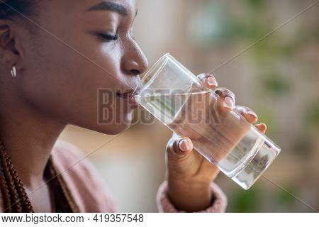 Body Hydration Concept. Closeup Of Black Millennial Female Enjoying Mineral Water