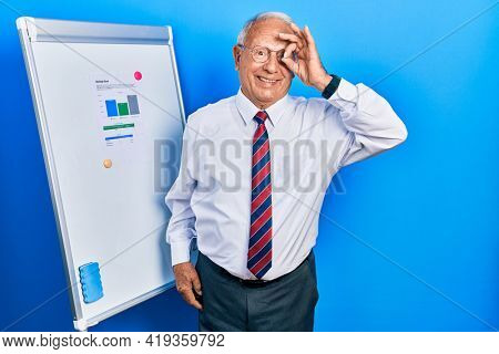 Senior man with grey hair standing by business blackboard doing ok gesture with hand smiling, eye looking through fingers with happy face.