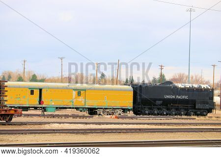 April 26, 2021 In Cheyenne, Wy:  Vintage Locomotive And Rail Car On A Train Track Taken At A Railroa
