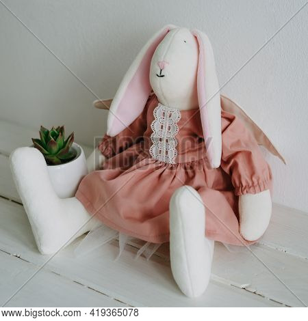 A Plush Hare In A Pink Dress Sits On A Wooden Surface. Succulent In A White Pot. The Hare Is Plush W
